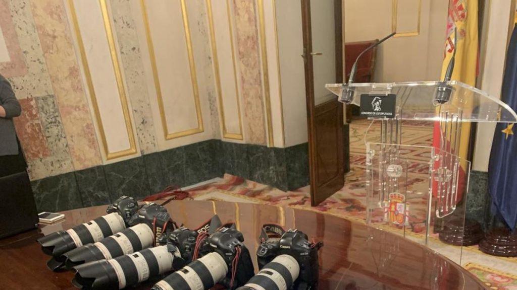 Las cámaras de los reporteros gráficos sobre el escritorio como gesto de protesta. FOTO: InfoLibre.es