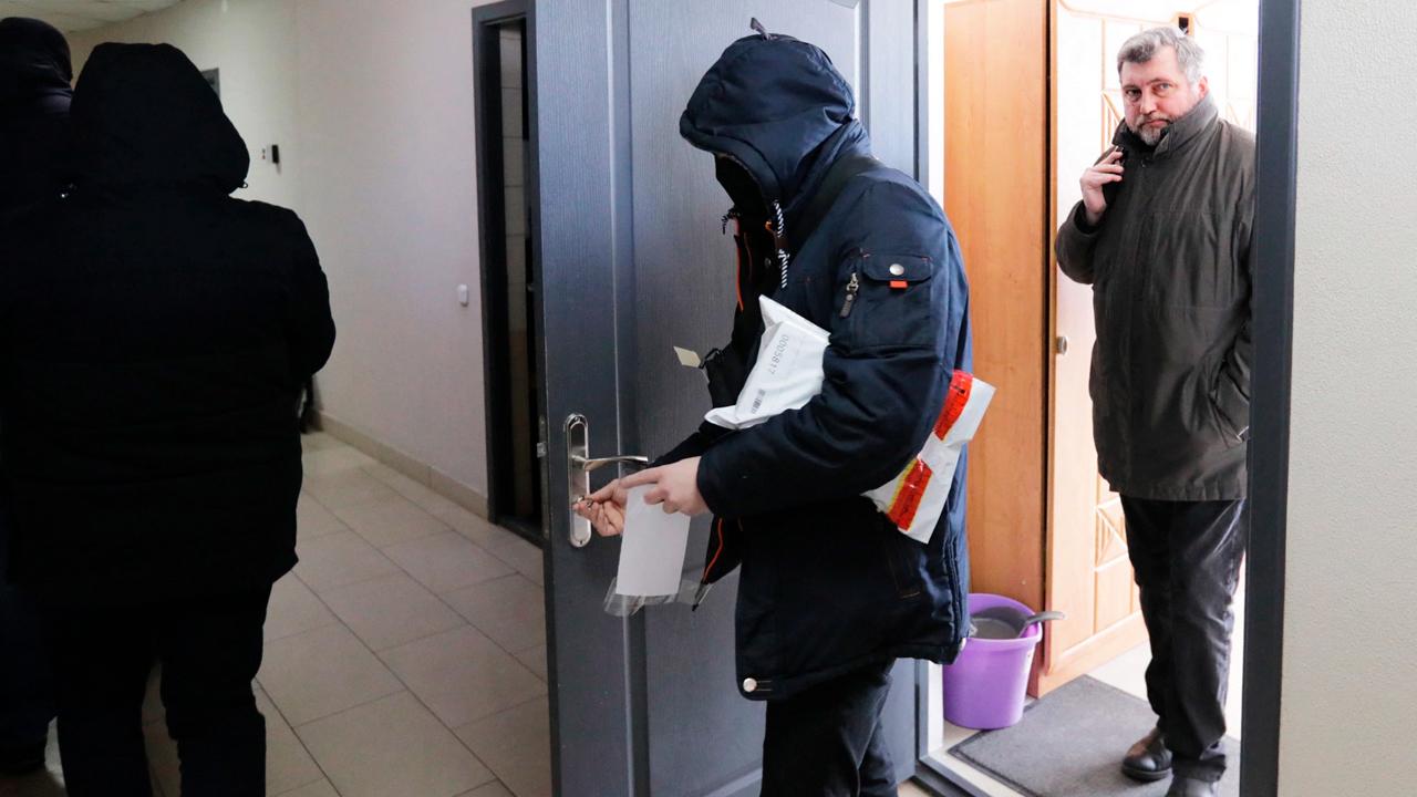 El director de la Asociación Bielorrusa de Periodistas (BAJ), Andrei Bastunets (derecha), sale de la oficina de la BAJ después de que la policía la allanara el 16 de febrero de 2021. (AFP)